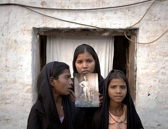 The daughters of Asia Bibi with an image of their mother, standing outside their residence in Sheikhupura on November 13, 2010.