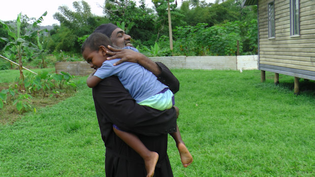 Fr. Barnabas greeted by a child.