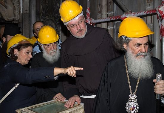 Chief Scientific Supervisor Antonia Moropoulou shows the exposed tomb to (from left) representatives of the Armenian Patriarch Nourhan Manougian and Franciscan Custos Fr. Francesco Patton, and Thephilos III, the Greek Patriarch of Jerusalem. PHOTOGRAPH BY ELISAVET TSILIMANTOU, JERUSALEM PATRIARCHATE - NATIONAL TECHNICAL UNIVERSITY OF ATHENS