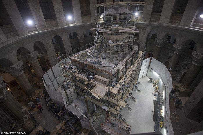 A view of the tomb and its shrine, surrounded by construction works. The burial slab was enclosed in an 18th century shrine structure known as the Edicule – a word derived from the Latin term aedicule meaning 'little house'. These steel girders supporting the Edicule will be removed when restoration work is finished next spring