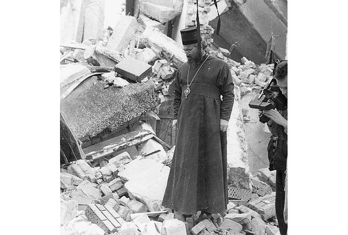 """Православни свештеник поред срушене цркве у Петринји 1991. године (Фото: Архива """"Политике"""")"""