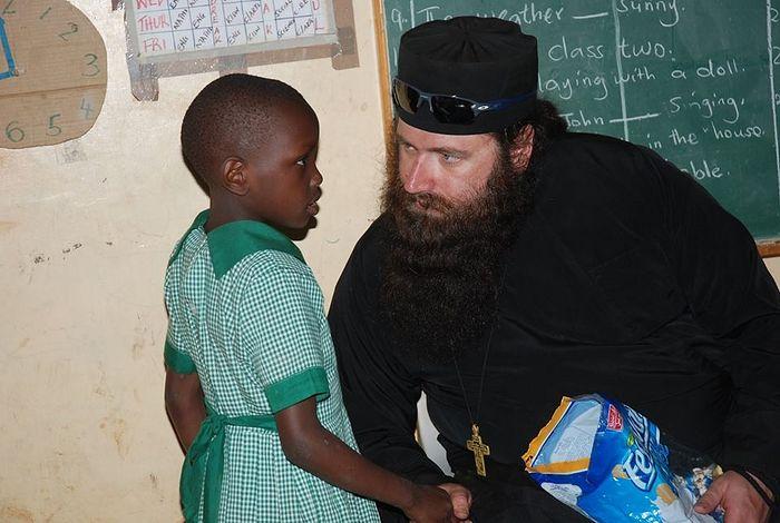 Отец Силуан общается с одним из детей Киберы в образовательном центре святого Георгия