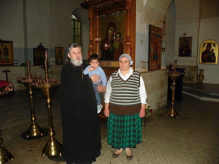 Протоиерей Феодор (Хуцишвили), матушка Нина и внук Георгий рядом с чудотворной Казанской иконой Пресвятой Богородицы