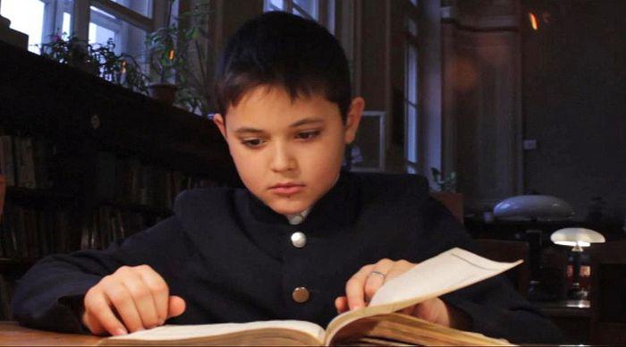 """Мальчик читает статистику из случайно найденной в библиотеке книги """"Список насельных мест Российской Империи"""""""