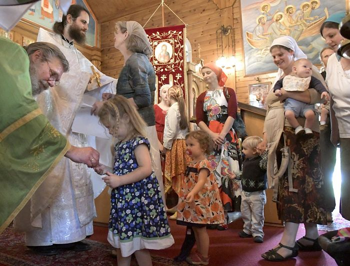 Nathan Williams, second from left, is greeted Sunday by his mother, Cindy, after his elevation to the priesthood in the Russian Orthodox Church during services at the Saint Alexander Nevsky Church in Richmond. Staff photo by Andy Molloy