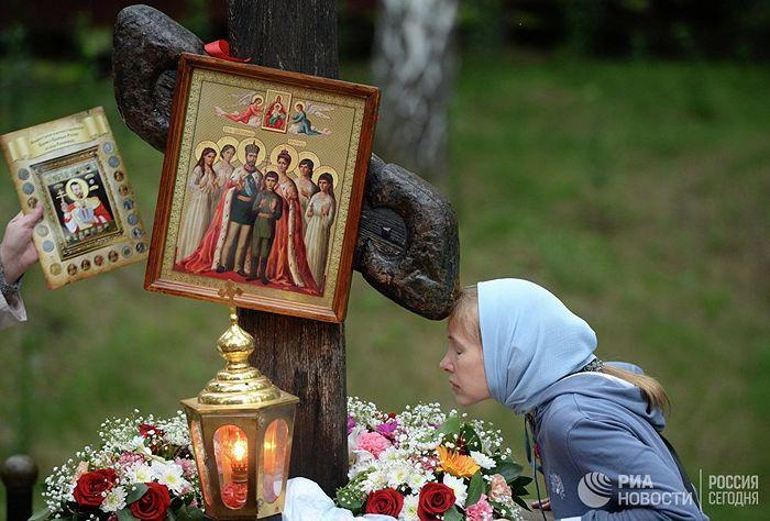 Женщина у поклонного креста на Ганиной Яме. © РИА Новости / Павел Лисицын