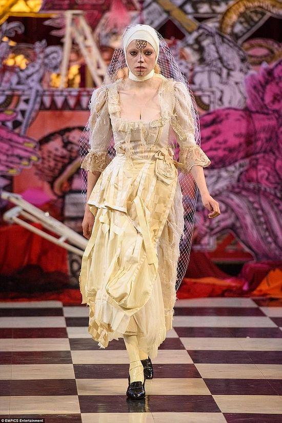 Модель облачена в платье невесты с белой вуалью; на ее лице выведен знак сигил