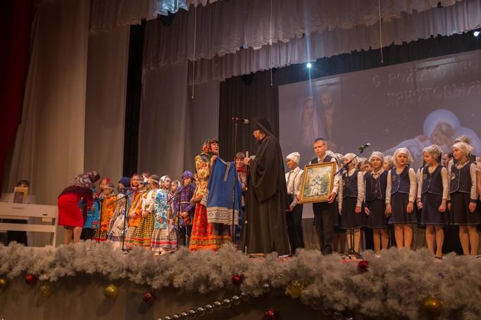 Марина Ростокина вручает традиционный русский костюм Епископу Югорскому и Няганьскому Фотию