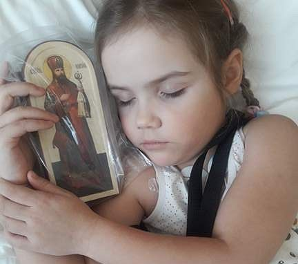 Anna sleeping in the hospital with an icon of St. Hilarion Troitsky from Sretensky Monastery