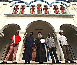 Иеромонах Дамаскин (Цагирис) с священником Сильвестром Сахиугуву и  прихожанами у врат храма